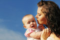 Happy mother kissing baby over blue sky Royalty Free Stock Photo