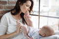 Happy mother kissing the feet of a newborn baby Royalty Free Stock Photo