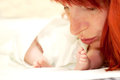 Happy mother kissing newborn baby the tiny feet of her who is sleeping in bed Royalty Free Stock Photo