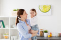 Happy mother and little baby girl at home kitchen Royalty Free Stock Photo