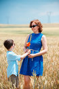Happy mother with little son walking happily in wheat field