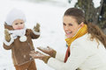 Happy mother playing with baby in winter park high resolution photo Royalty Free Stock Photography