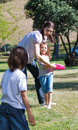 Happy mother playing Frisbee with her children Royalty Free Stock Photo