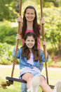 Happy mother pushing daughter on swing in playground Royalty Free Stock Photography