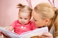 Happy mother read a book to baby girl Royalty Free Stock Photo