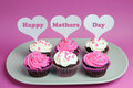 Happy mother s day message across white heart toppers on pink and white decorated red velvet cupcakes background Royalty Free Stock Images