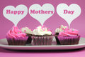 Happy mother s day message on pink and white decorated cupcakes across heart toppers red velvet background Royalty Free Stock Images