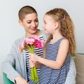 Happy Mother`s Day, Women`s day or Birthday background. Cute little girl giving mom, cancer survivor, bouquet of flowers. Royalty Free Stock Photo