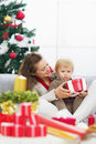 Happy mother showing baby christmas present box high resolution photo Royalty Free Stock Photos