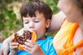 Happy mother with son eating chocolate snail cocoa outdoor Stock Photo