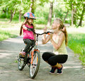 Happy mother talking with her daughter smiling, which teaches to biking Royalty Free Stock Photo