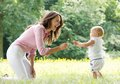 Happy mother teaching baby to walk in the park portrait of a Stock Image