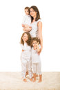 Happy mother with three children posing home and standing on carpet Stock Image