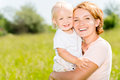Happy mother and toddler son outdoor portrait in the spring meadow Royalty Free Stock Image