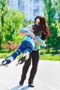 Happy mother twirling her son at the city garden Stock Image