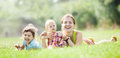 Happy mother with two children in grass at summer park Stock Image