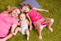 Happy mother and two children lie on green carpet top view Stock Image