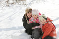Happy mother with two children lying in snow copy space Royalty Free Stock Images