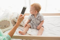 Happy mother using her phone with her baby boy Royalty Free Stock Photo