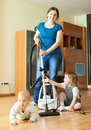 Happy mother wth two children cleans at home living room with vacuum cleaner Royalty Free Stock Photography
