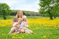 Happy Mother and Young Children Relaxing in Flower Meadow Royalty Free Stock Photo
