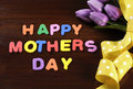 Happy mothers day childrens toy block colorful letters spelling greeting on dark rustic wood table with purple pink tuplis and Royalty Free Stock Photography