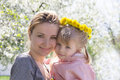 Happy mothre and baby girl in spring garden with dandelion wreath Royalty Free Stock Images