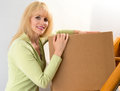 Happy mover woman pauses moving boxes up the stairs in a house Stock Photography