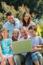 Happy multi generation family with a laptop sitting in park on bench Royalty Free Stock Photos