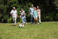 Happy multi generation family playing football together in the park Stock Images