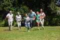 Happy multi generation family running towards camera in the park on sunny day Royalty Free Stock Image