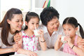 Happy multi generations asian family at home drinking milk beautiful grandmother mother and granddaughters healthcare concept Royalty Free Stock Images