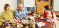 Happy multigeneration family communicate over table holiday at home interior Stock Images