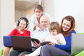 Happy multigeneration family together few electronic communication devices home Royalty Free Stock Photography