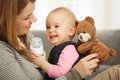 Happy mum baby girl laughing cuddling holding teddy bear Royalty Free Stock Photos