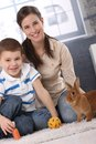 Happy mum and little son playing with rabbit Royalty Free Stock Images