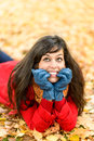 Happy nervous girl on autumn thinking woman day and looking up naughty surrounded by golden leaves lying down and smiling Royalty Free Stock Photography