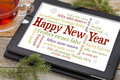 Happy new year in different languages on a digital tablet with a cup of tea and spruce twigs Stock Photography
