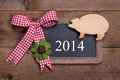 Happy new year greeting card on a wooden background with lucky pig and green clover with red checked ribbon Royalty Free Stock Photos