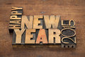 Happy new year greetings text in vintage letterpress wood type blocks on a grunge wooden background Stock Image