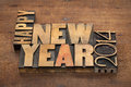 Happy new year greetings or wishes text in vintage letterpress wood type blocks on a grunge wooden background Royalty Free Stock Photo