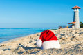 Happy  New Year holidays at Sea. Santa hat on sandy beach - christmas holiday concept Royalty Free Stock Photo
