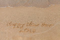 Happy New Year 2017 - the inscription on the sand beach with a soft wave.