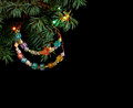 Happy New Year and Merry Christmas hand made craft colorful beaded letter garland on Christmas tree branch Royalty Free Stock Photo