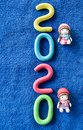 Happy New Year 2020 , molding of color clay with little girls toys on blue background. Royalty Free Stock Photo