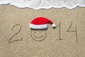 Happy new year 2014 with smiley face in christmas hat on sandy b Royalty Free Stock Photo