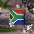 Happy New Year tag with South Africa flag on pillow. Christmas decoration concept on wooden table with lovely objects