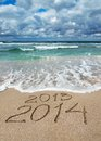 Happy New Year 2014 wash away 2013 concept on sea beach Royalty Free Stock Photo