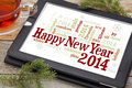 Happy new year word cloud on a digital tablet with a cup of tea and spruce twigs Stock Photo