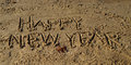 Happy new year words written in sand the on the beach Stock Images